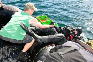 LS Litter helps fellow diver LS Marc Andre Ouimet get into the water for a dive