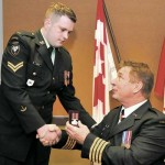 Honorary Colonel Rick Hansen presents the Sacrifice Medal to Cpl Darryl Hansen.