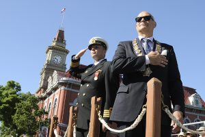 Victoria Mayor, Mr Dean Fortin (Right) and CFB Esquimalt Base Commander, Capt(N) Luc Cassivi (Left) salute the parade from the dais at Centennial Square, Victoria, BC while the participants march past during the 116th Annual Victoria Day Parade.