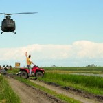 A CH-146 Griffon helicopter investigates flood damage near Portage la Prairie, Manitoba during OpLENTUS on July 7, 2014.